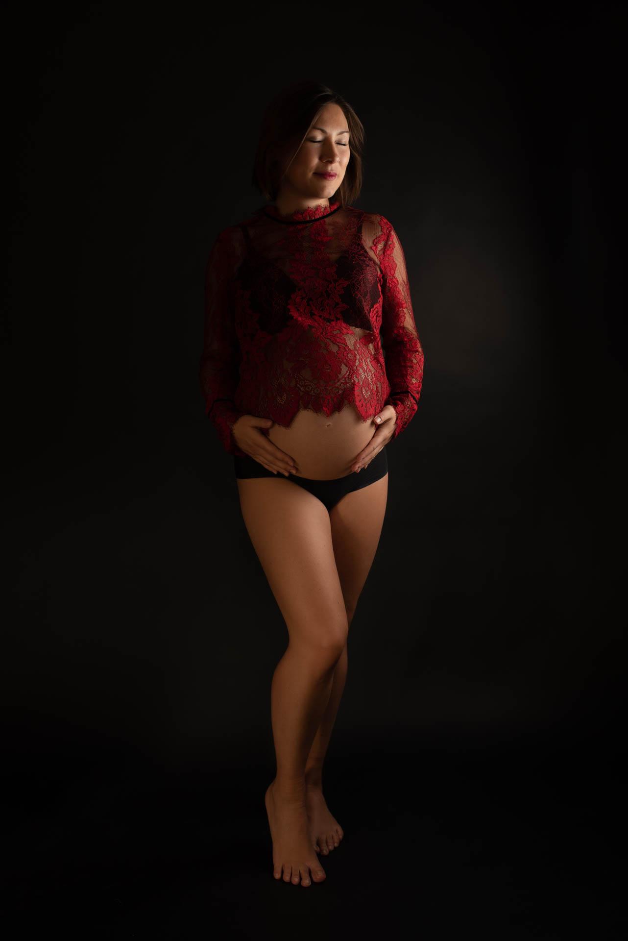 Schwangerschaftsfoto in rotem Spitzentop im Fotostudio
