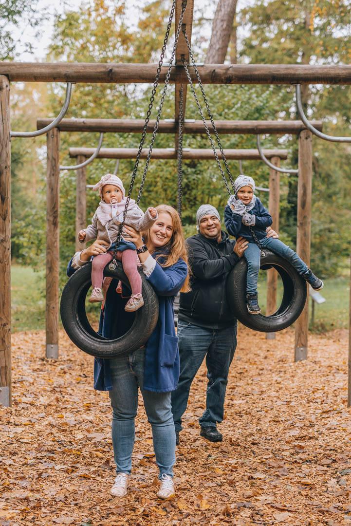 Familienfoto mit zwei Kindern auf Spielplatz