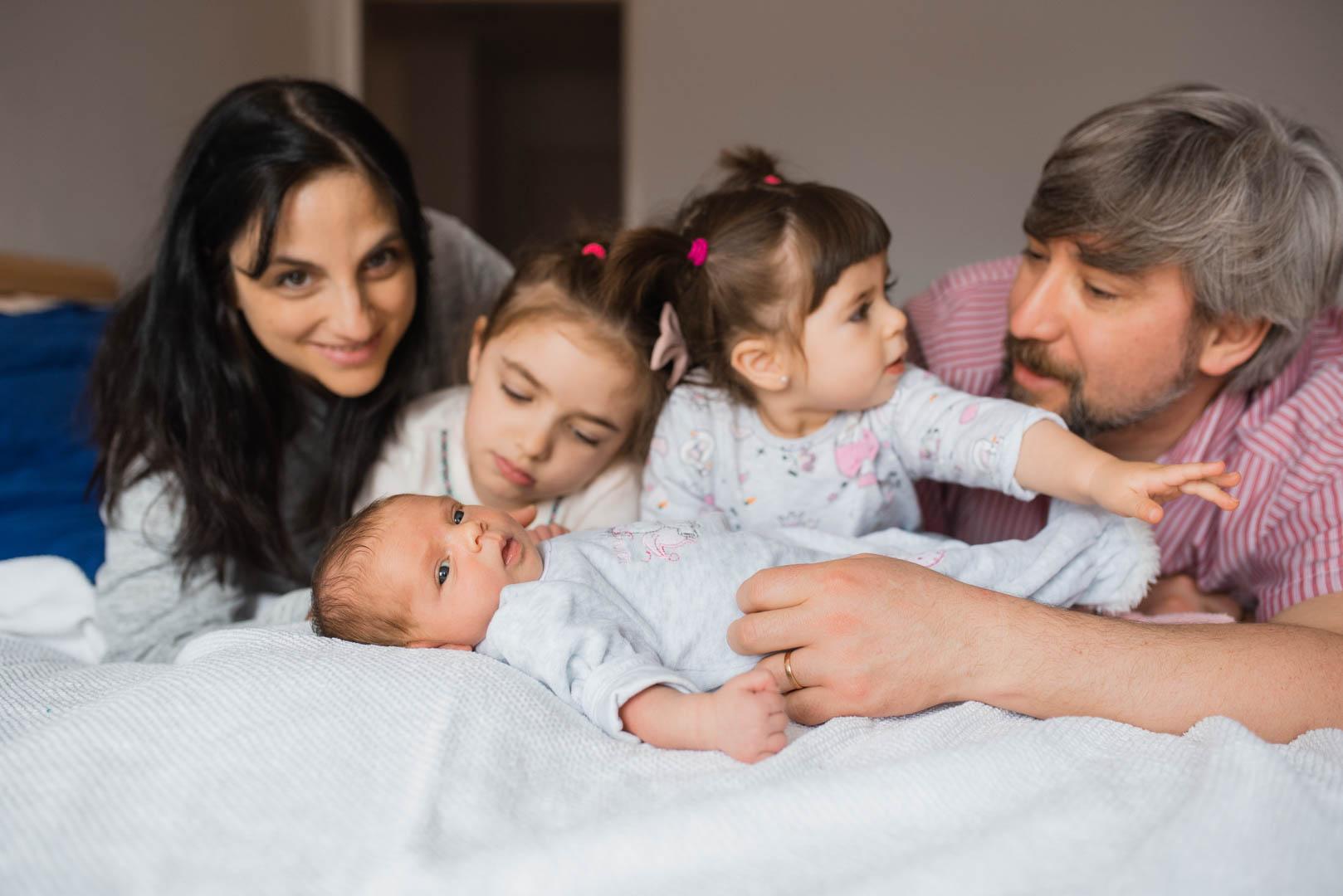 Familienfoto mit Neugeborenem im Schlafzimmer