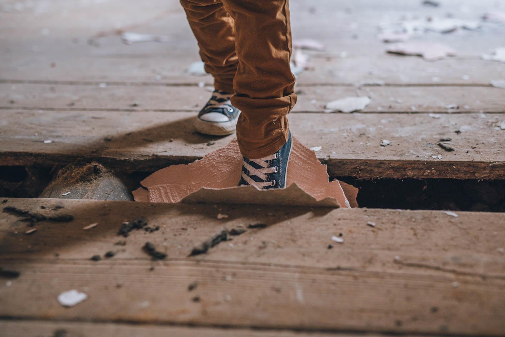 Kinderportrait Schuh tritt in Bodenspalte