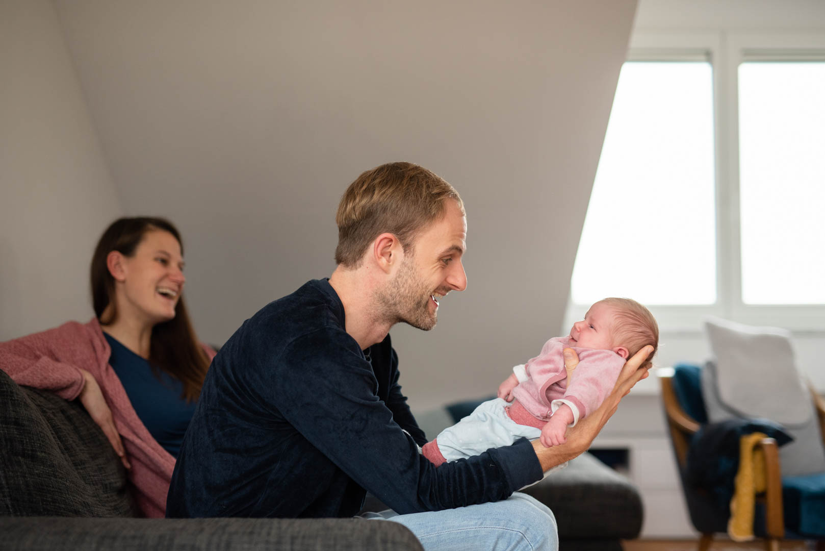 Homestory lachende Familie mit Baby